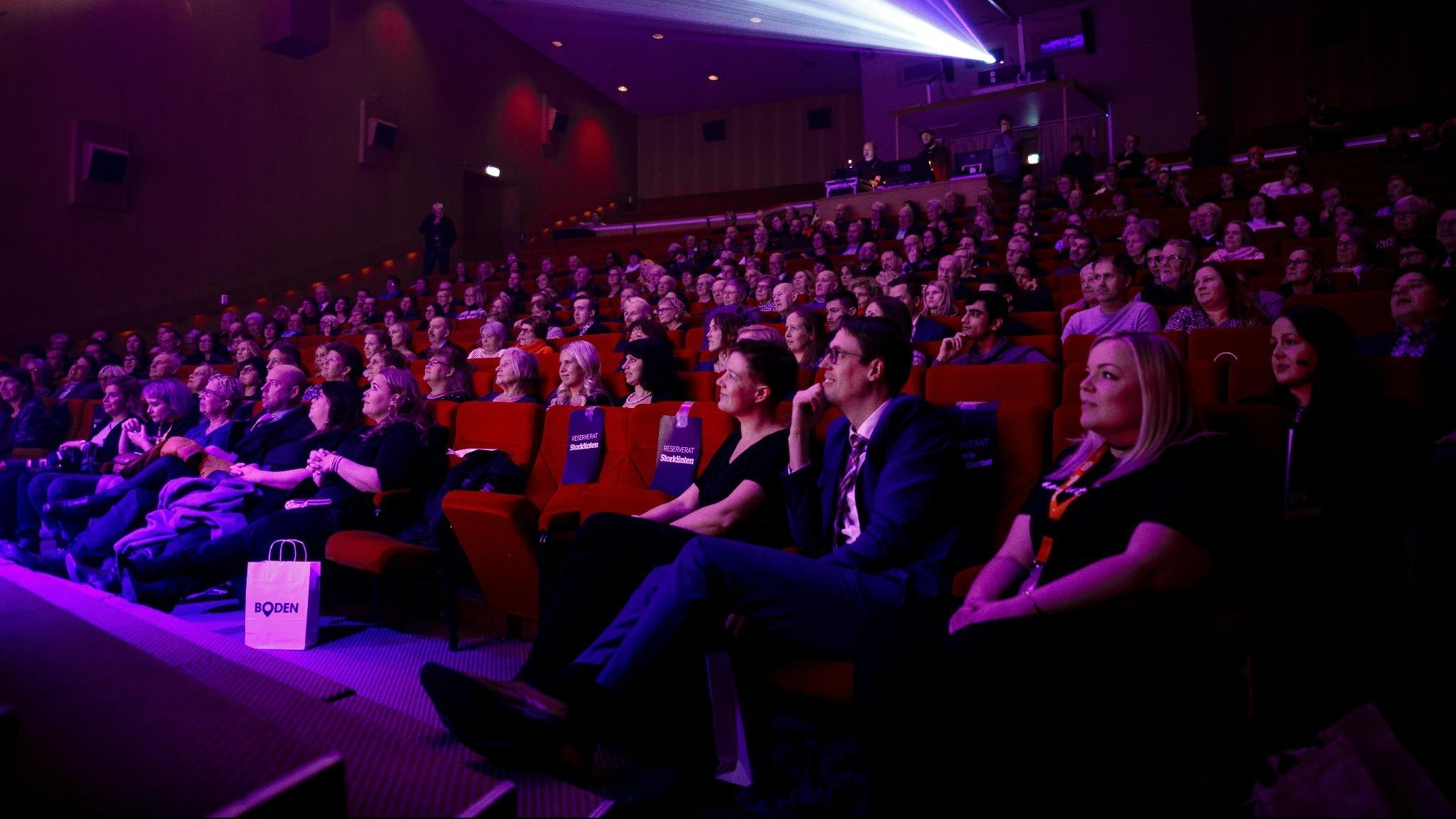 en stor mängd människor sitter i biograf och tittar mot skärmen.