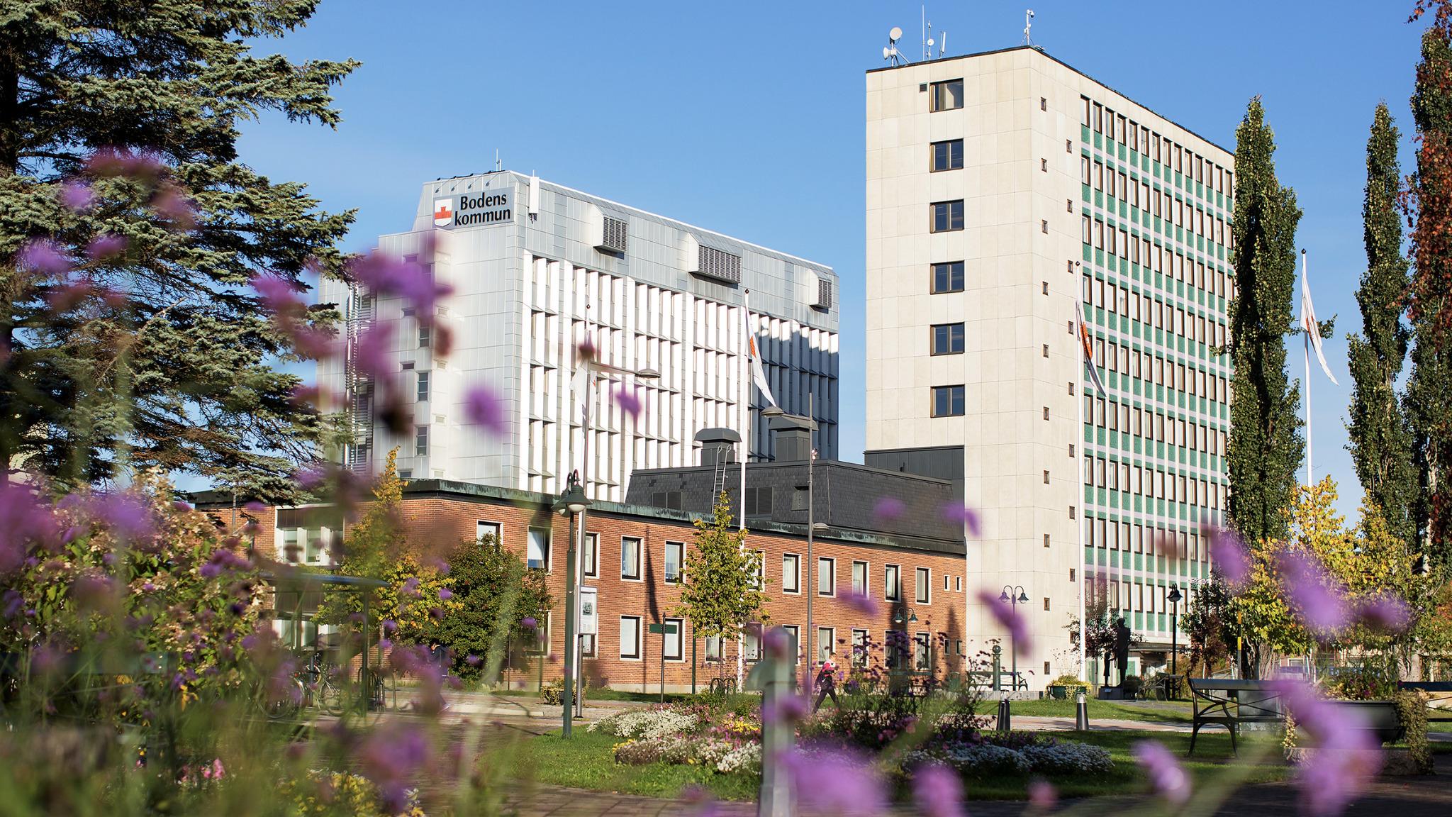 Bodens kommuns stadshus, två höga byggnader, med blommor i förgrunden.