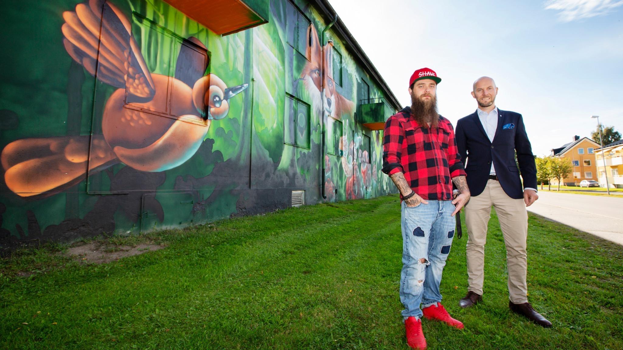 Ung man i skägg, röd keps och rödrutig skjorta och man utan hår i marinblå kostym framför en husfasad med en färgstark väggmålning som föreställer skog, en fågel, en räv och insekter.
