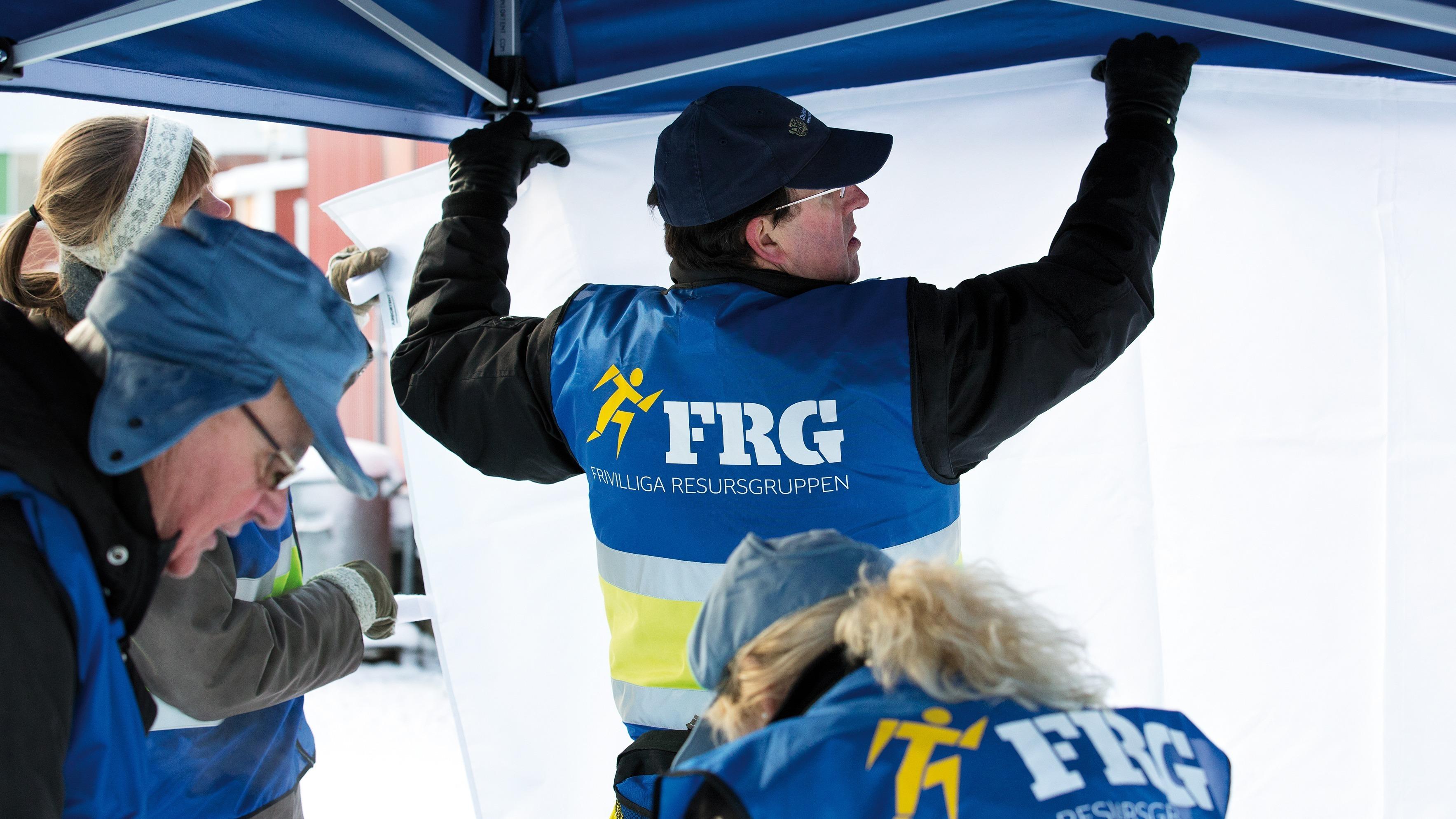 Fyra personer ur frivilliga resursgruppen som sätter upp ett tält.