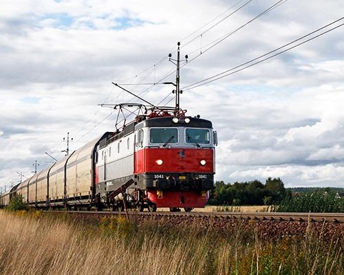 Tåg med röd front kör på räls.