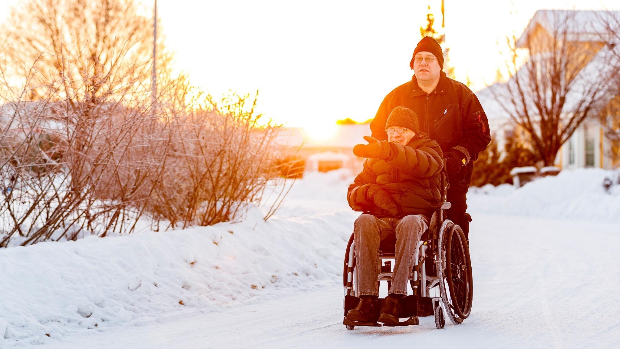 Man som skjuter en annan man i rullstol på en vinterväg.