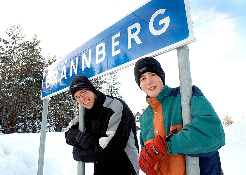 """Två ungdomar luta sig mot vägskylt på vilken det står """"Brännberg""""."""