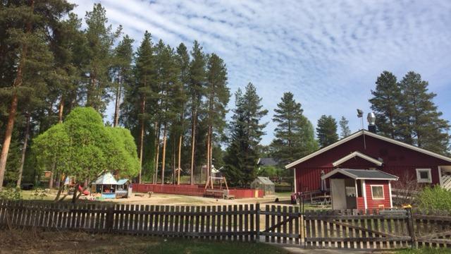 Röd byggnad och lekplats inhängnad av trästaket.