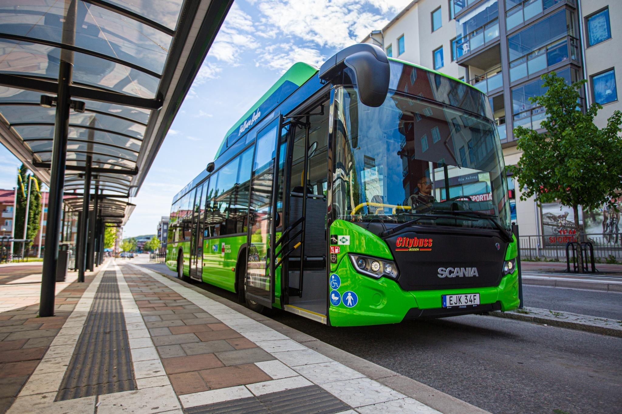 Grön stadsbuss vid hållplats i centrala Boden. Främre dörren är öppen.