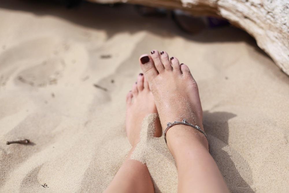 Bara fötter med nagellack i sand.