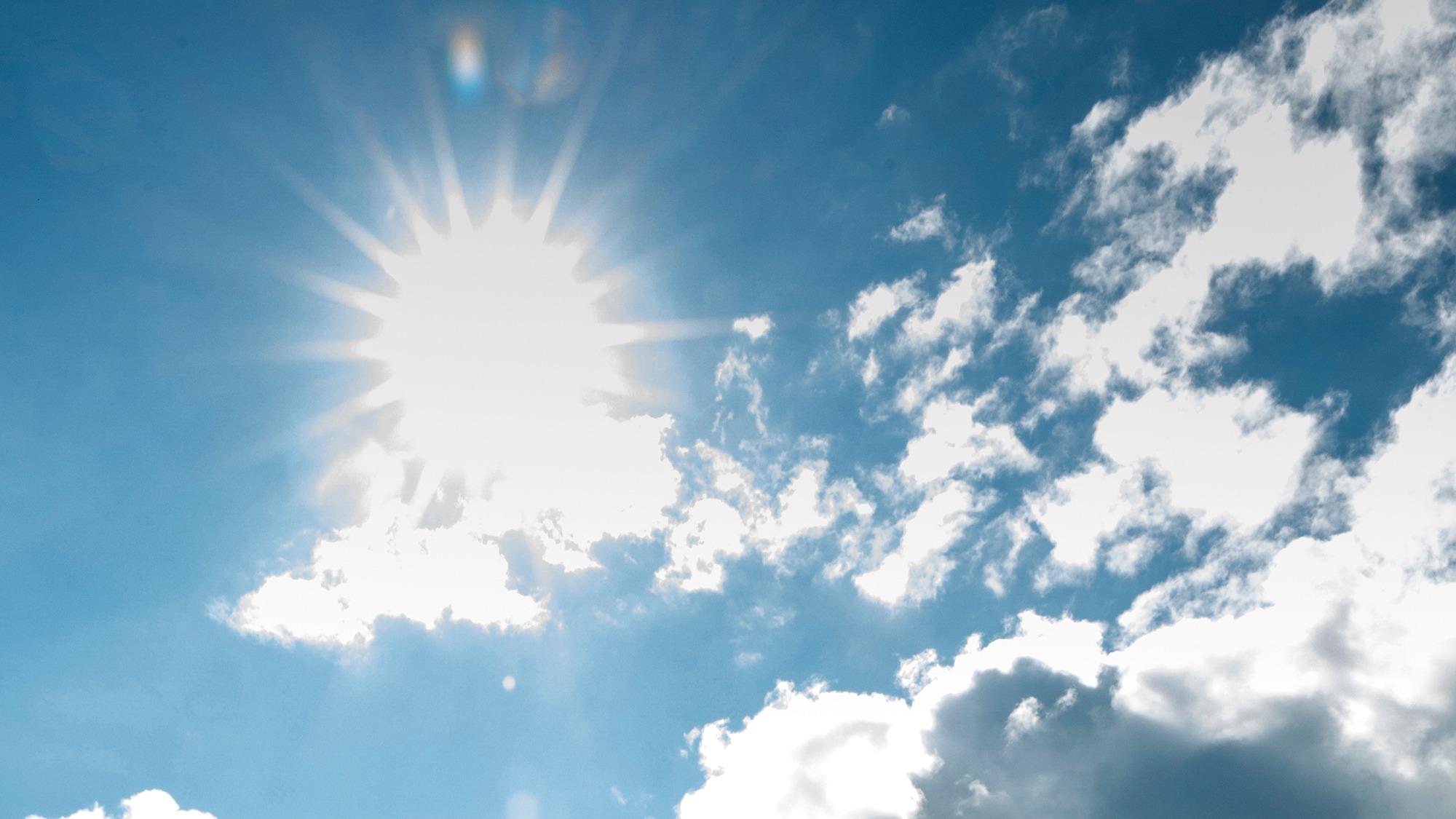 Sol lyser på blå himmel med några moln.
