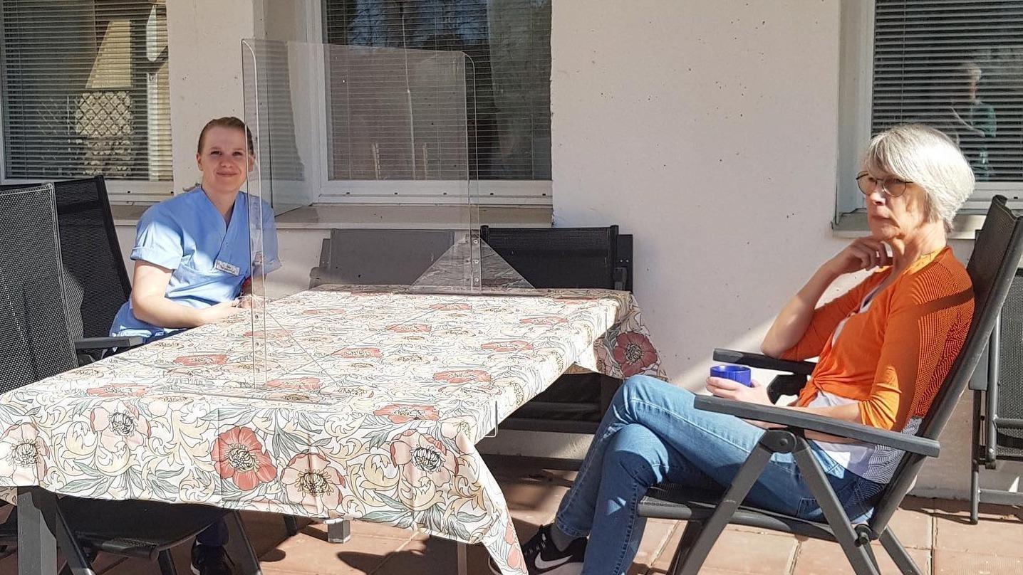 Två kvinnor på var sin sida om ett bord med plexiglas på.