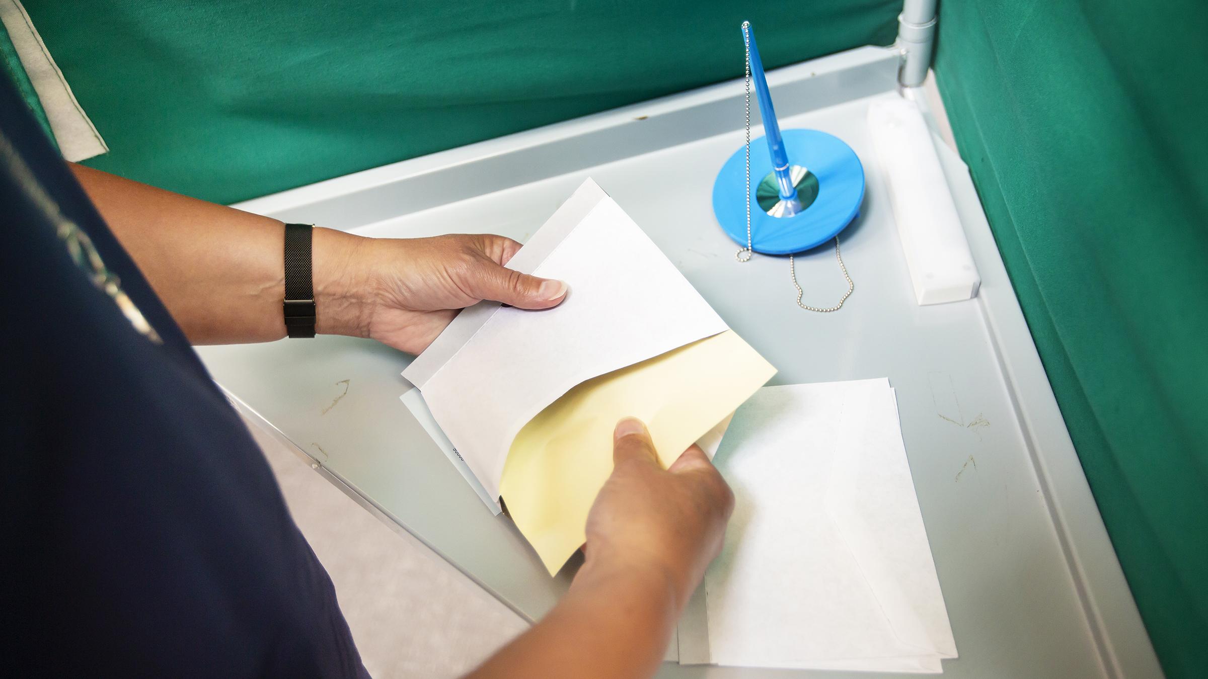 Gul röstsedel läggs i kuvert