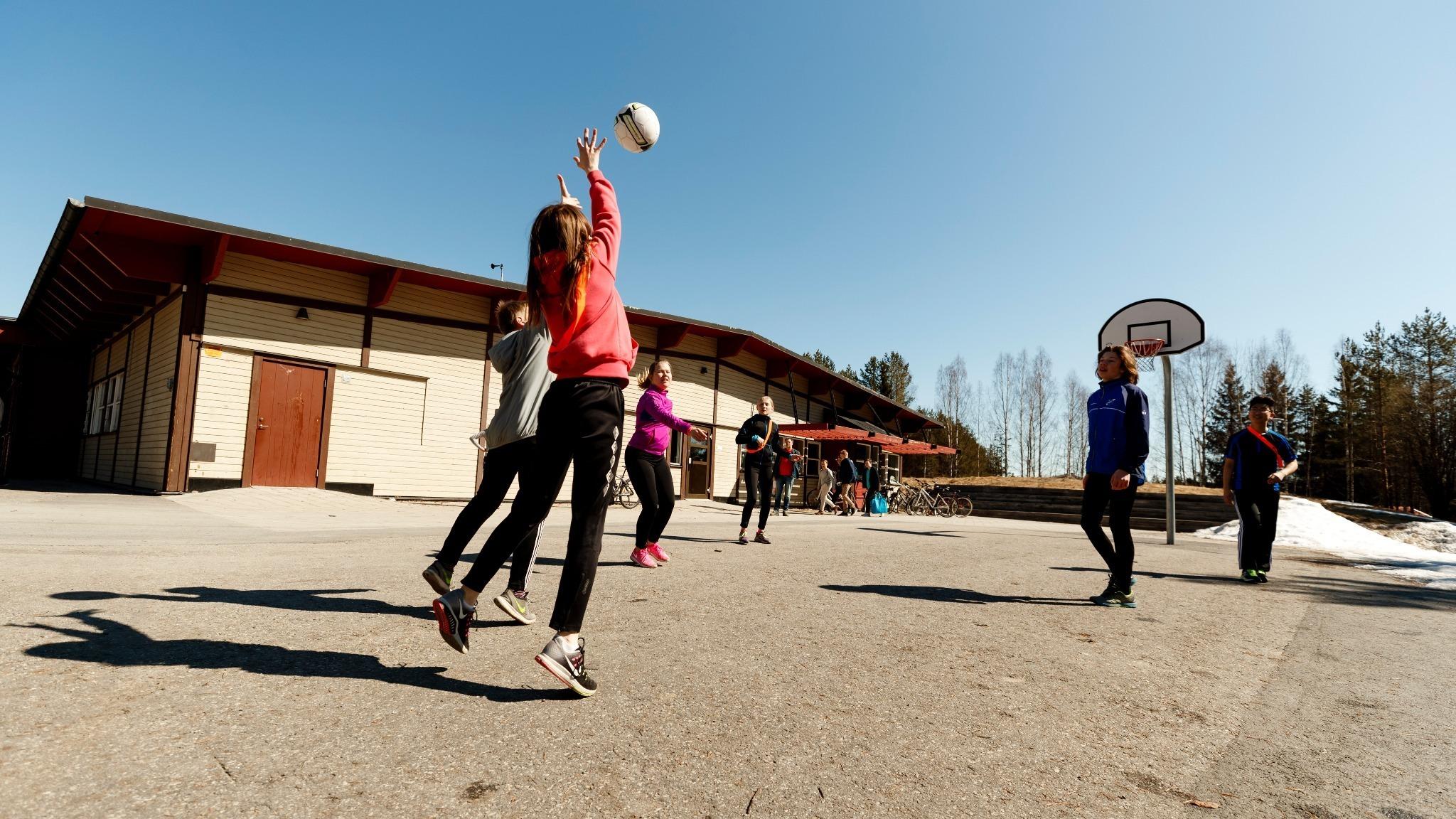 barn som spelar basket på en skolgård.