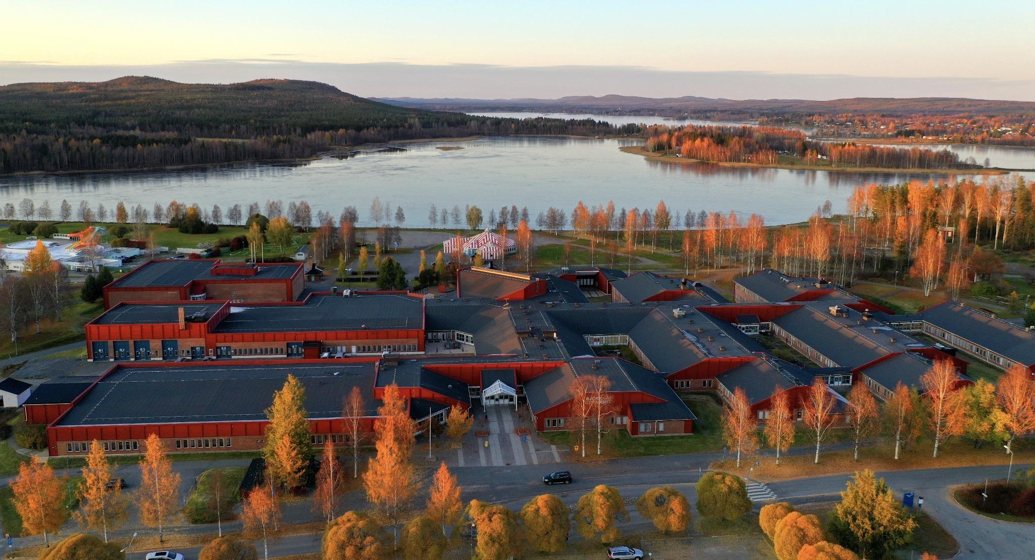 Flygfoto på Björknäsgymnasiet. Sjö i bakgrunden.