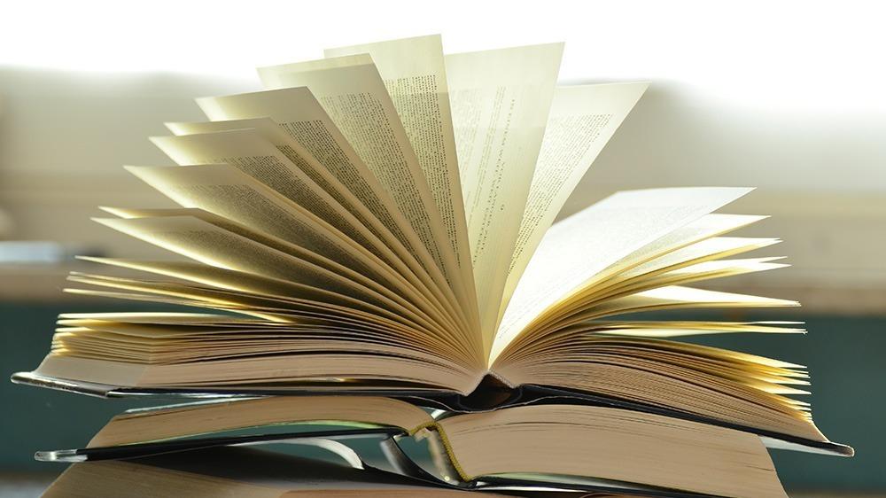 Två uppfällda böcker ligger på varandra.