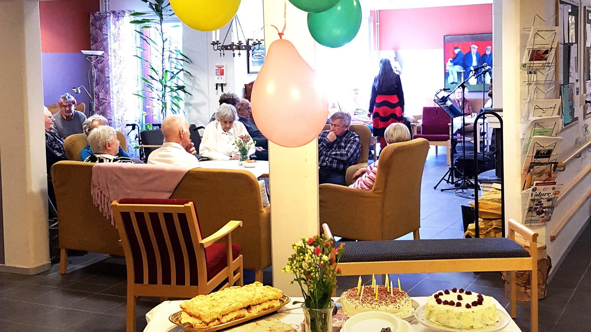 Äldre människor som sitter i soffan och äter tårta på Erikslunds äldreboende när boendet firade 10 år 2018.