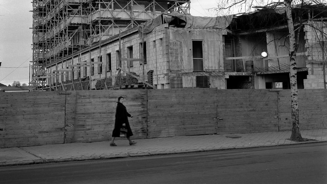Svartvit bild. Kvinna går framför byggarbetsplats.