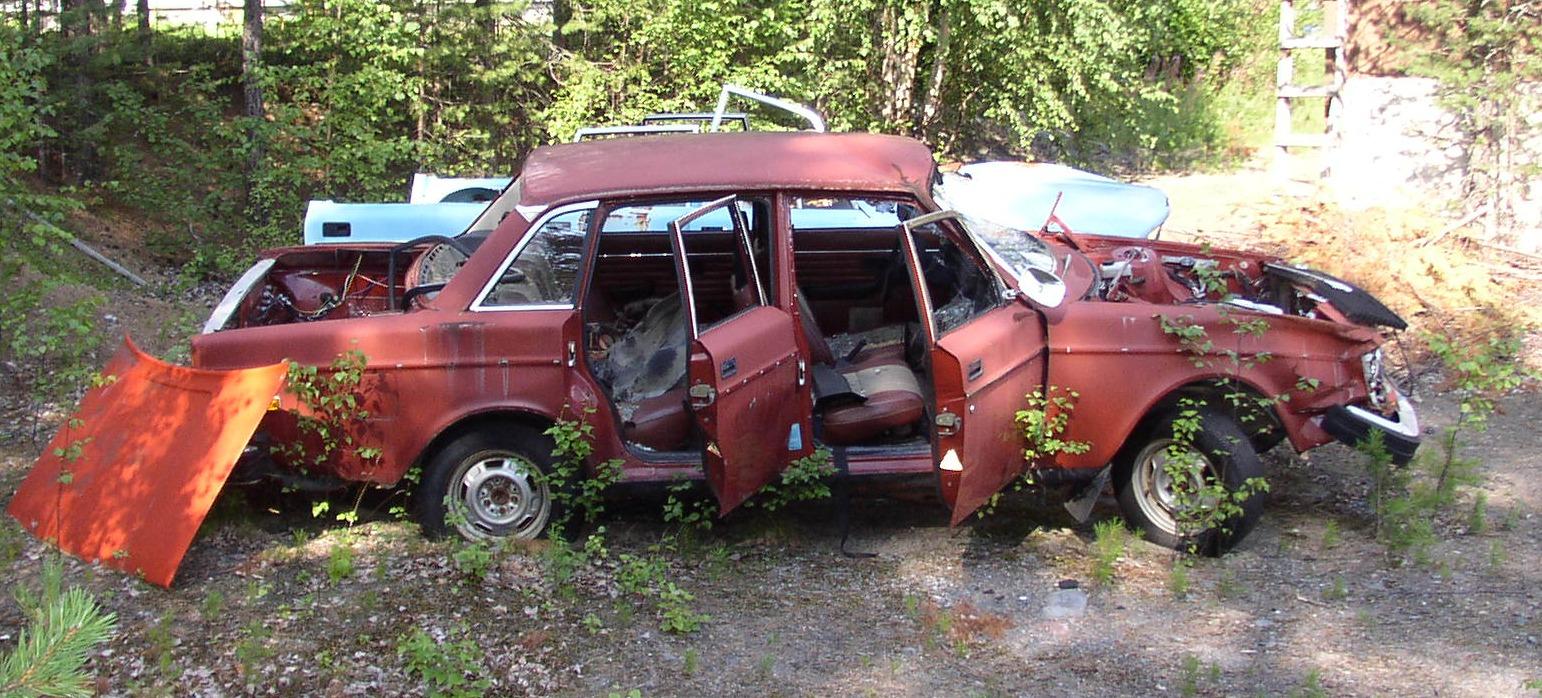 Röd Volvo 240 i väldigt dåligt skick.