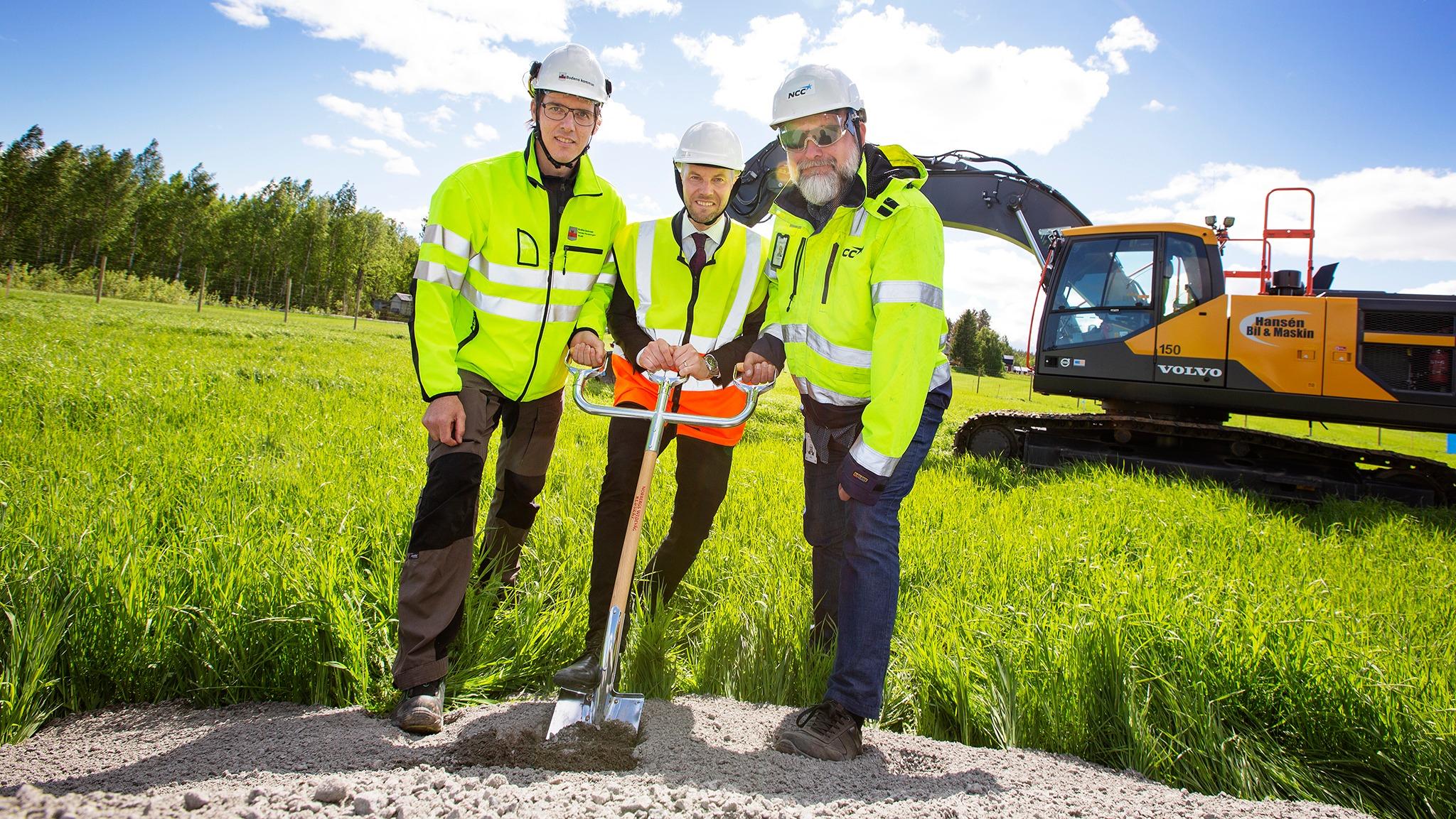 Tre personer i arbetshjälmar och varselkläder tar ett gemensamt spadtag framför en grävmaskin.