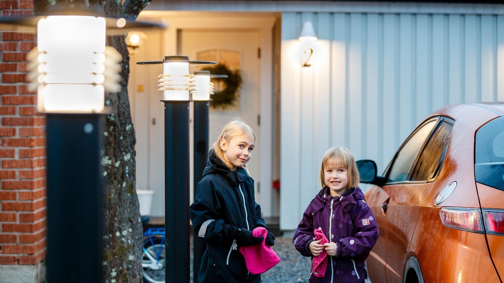 Två flickor står på uppfart framför hus. Till höger om dem står en bil.