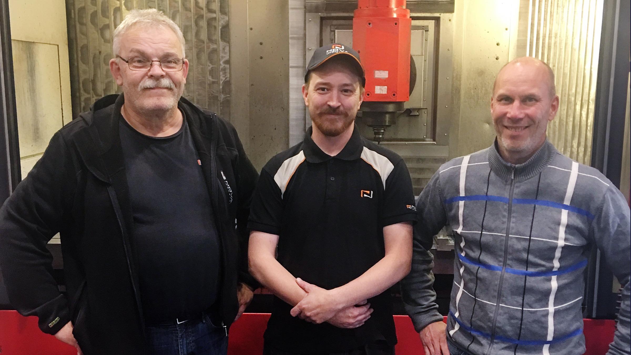 Tre män poserar i industrimiljö.