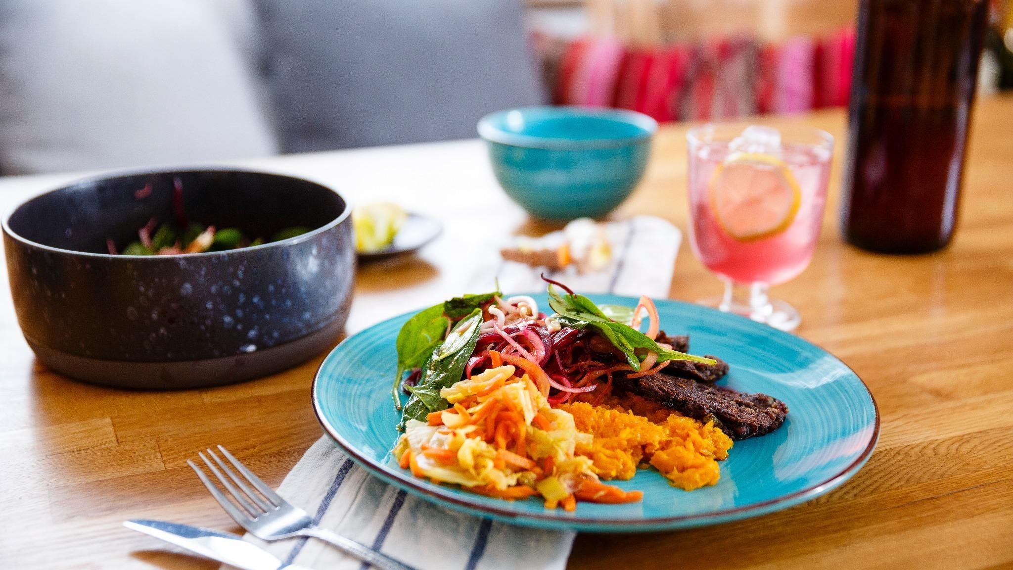 maträtt uppdukad på bord med bestick, glas, servett och tillbehör.