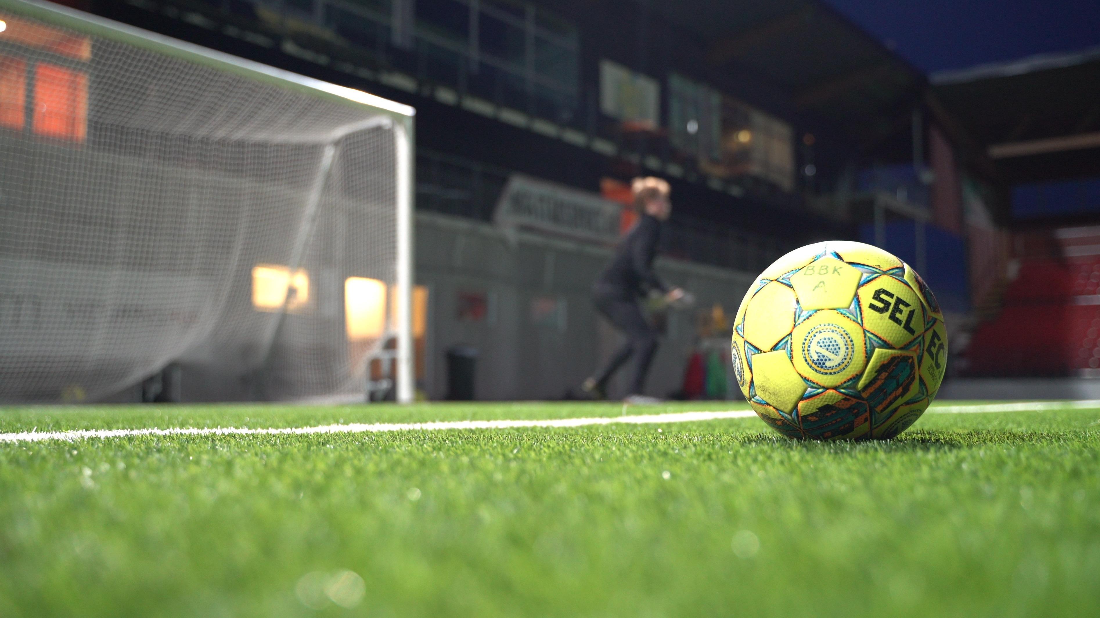 En gymnasieelev står i fotbollsmål. Närbild på en fotboll.