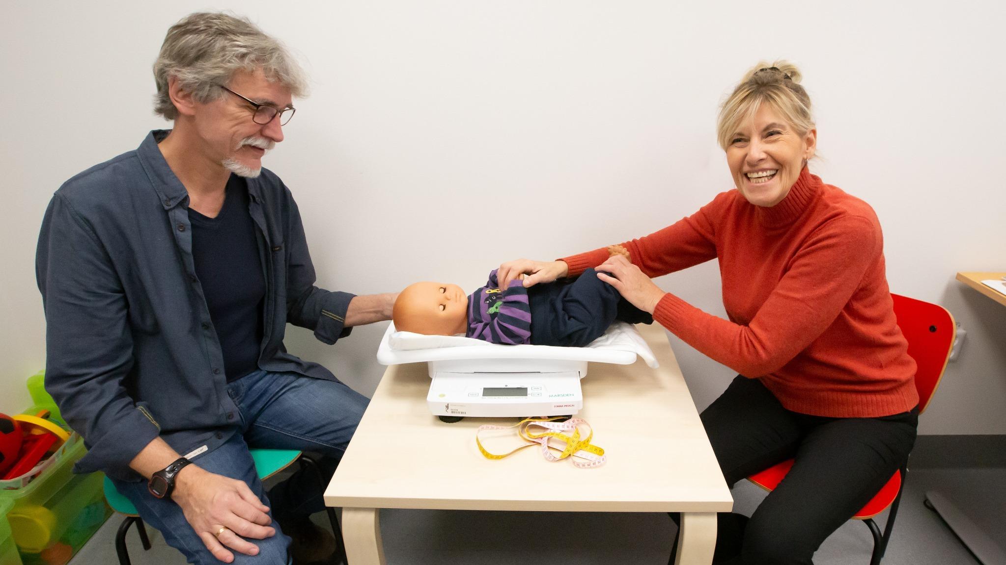 Personer som sitter vid ett skrivbord med en våg för att mäta en bebis på.