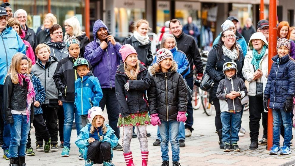 Stor folksamling i stadsmiljö. Såväl barn som vuxna på bilden.