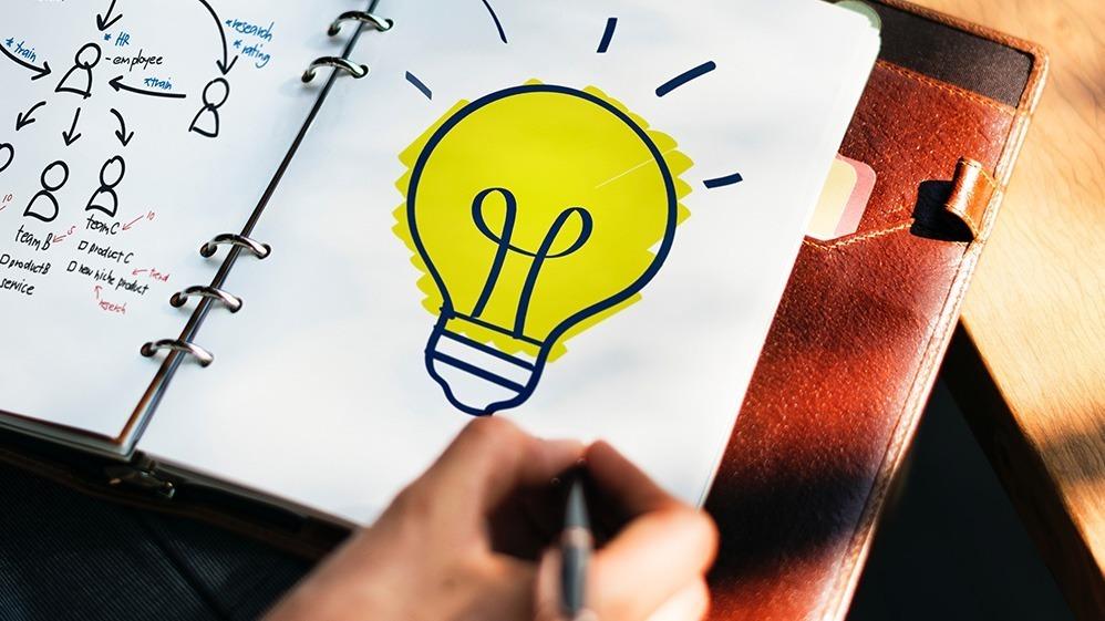 Person antecknar i anteckningsblock. Hen har ritat en lysande glödlampa.