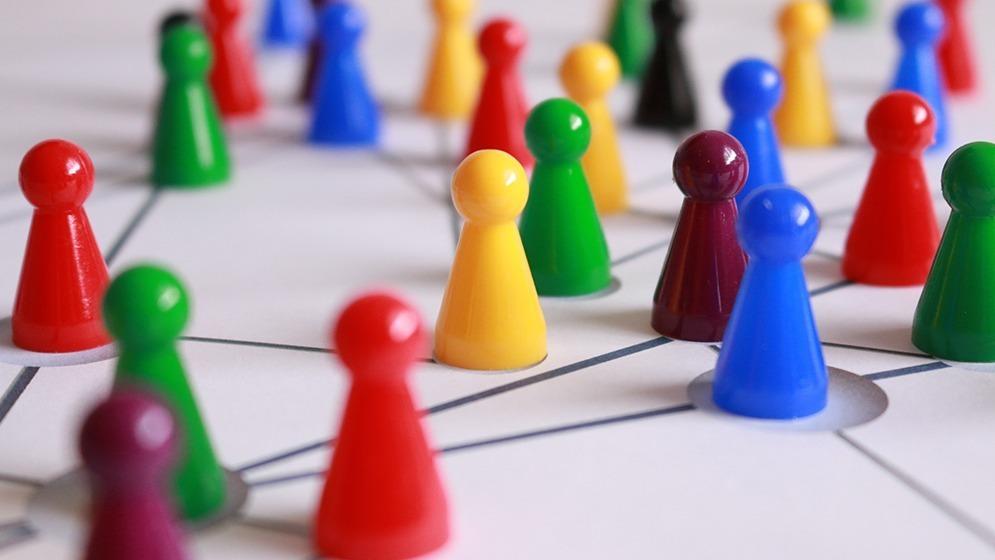 Spelpjäser i olika färger på en spelplan av ett brädspel.