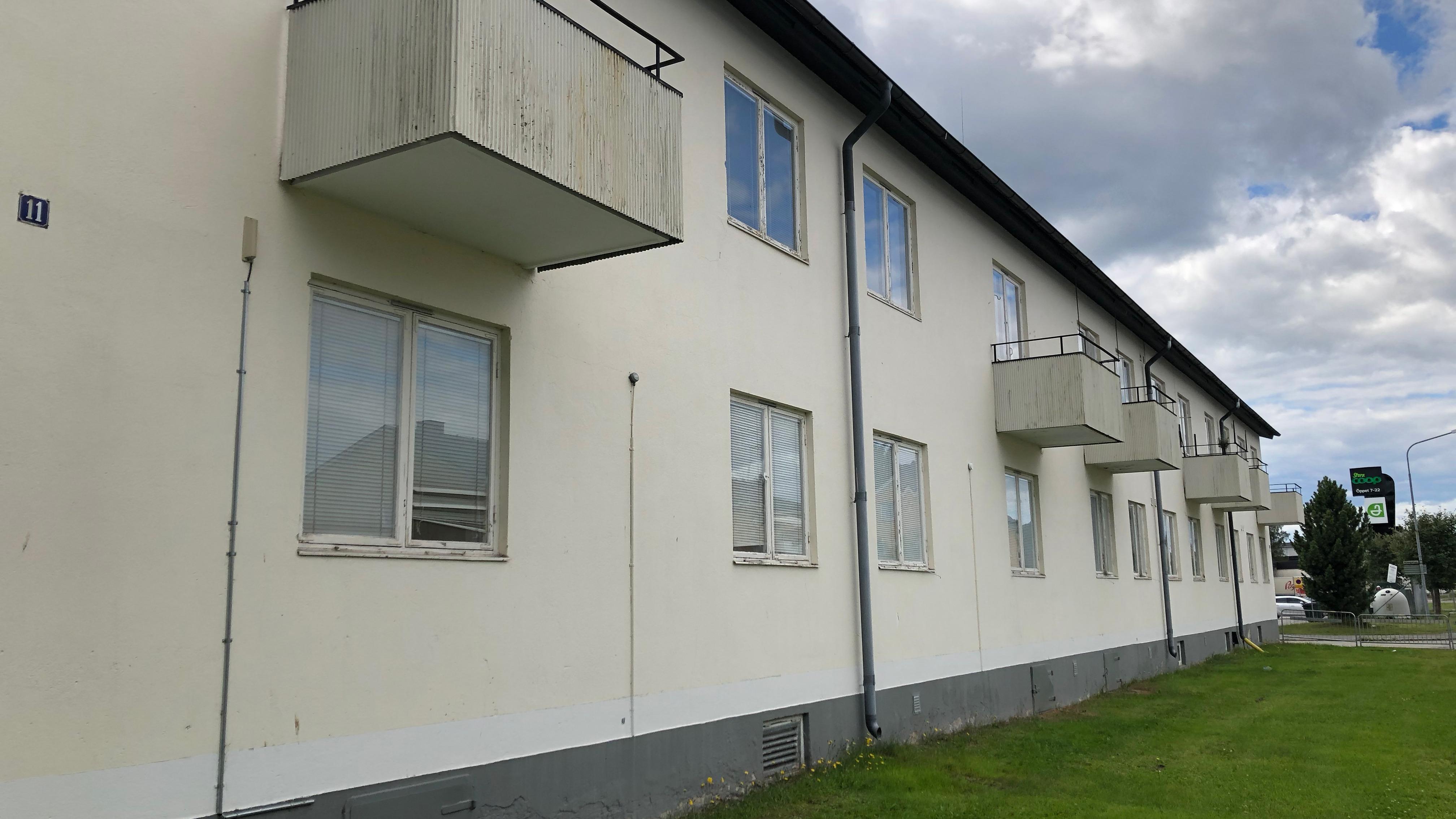 Vit, äldre fasad på flerfamiljshus längs Brogatan i centrala Boden