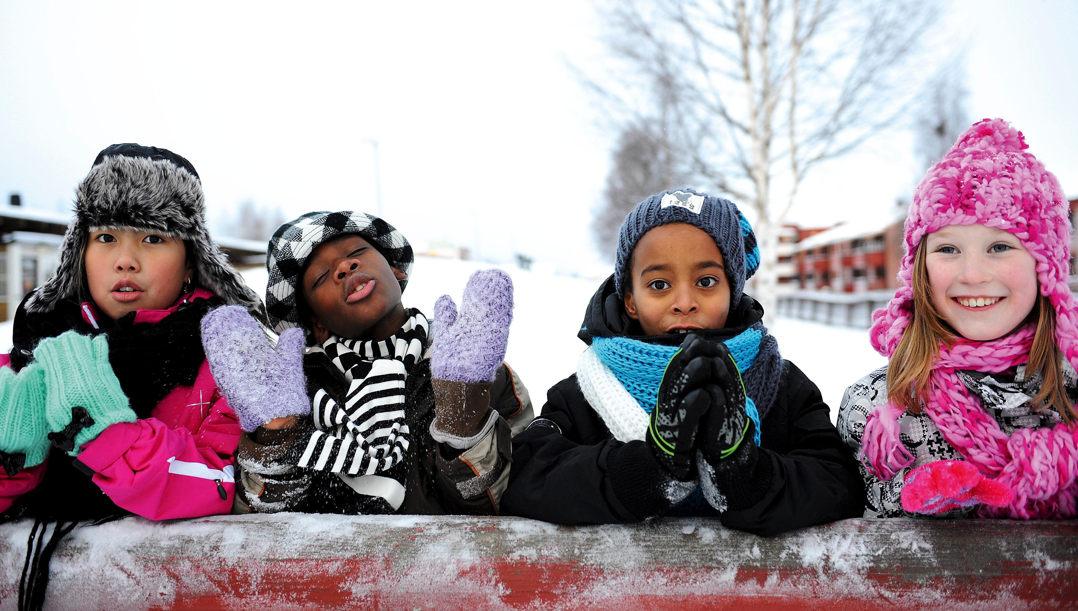 Vinterbild utomhus på fyra barn med mössor, vantar, halsdukar och varma jackor