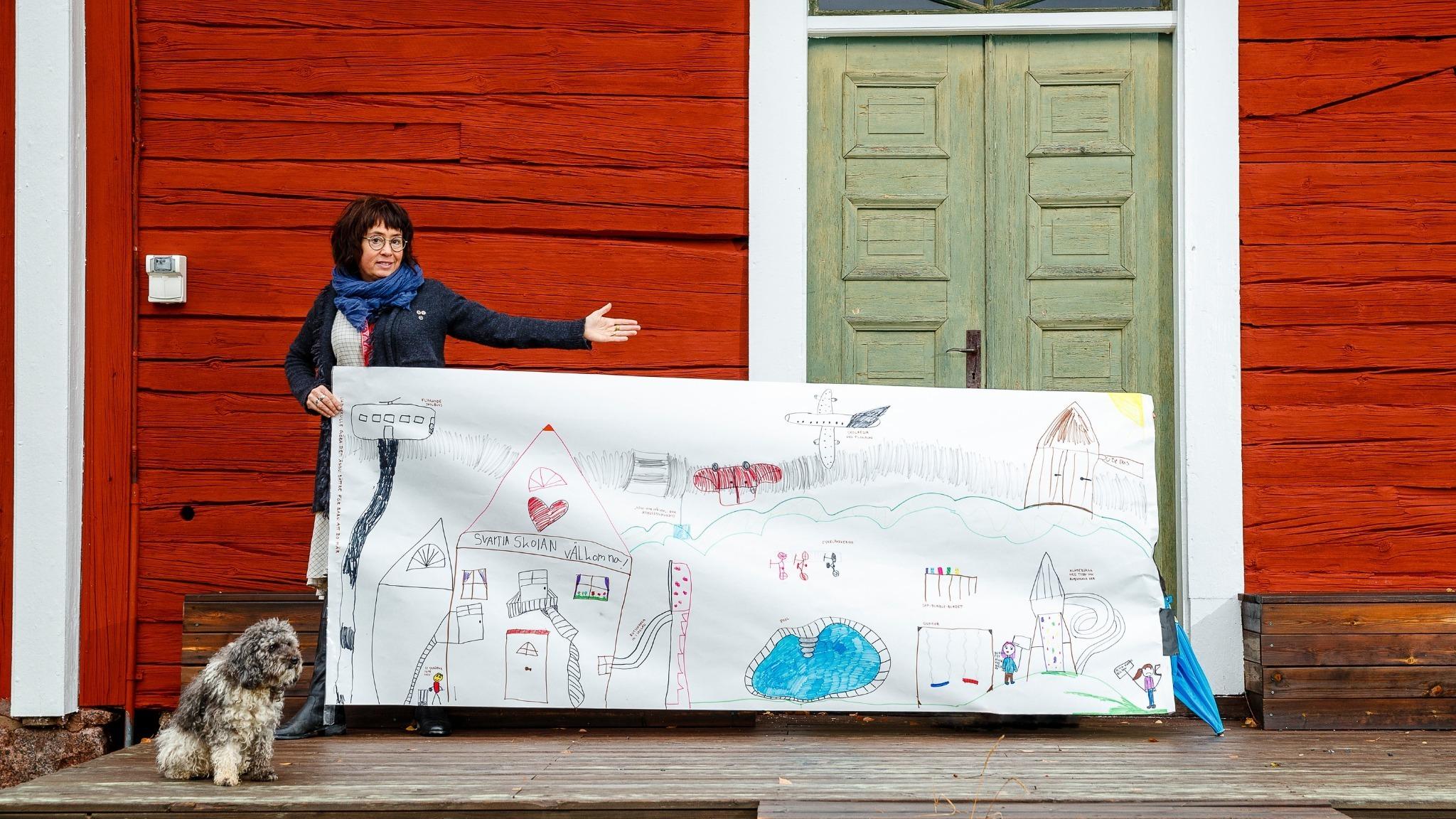 Kvinna står framför rött hus och visar upp en stor barnteckning.