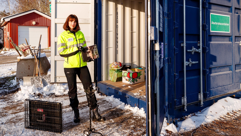 Kvinna i varseljacka står framför öppnad container.