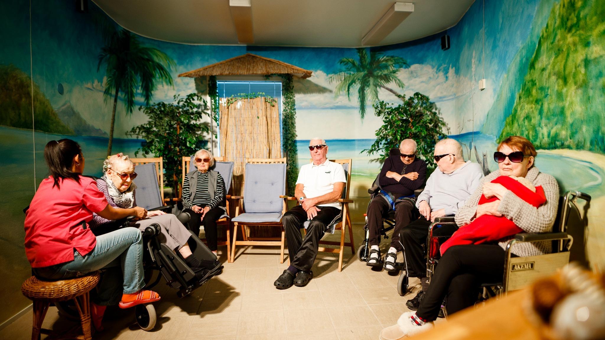 Pensionärer på äldreboende sitter i ett rum målat med stränder och palmer och solar.