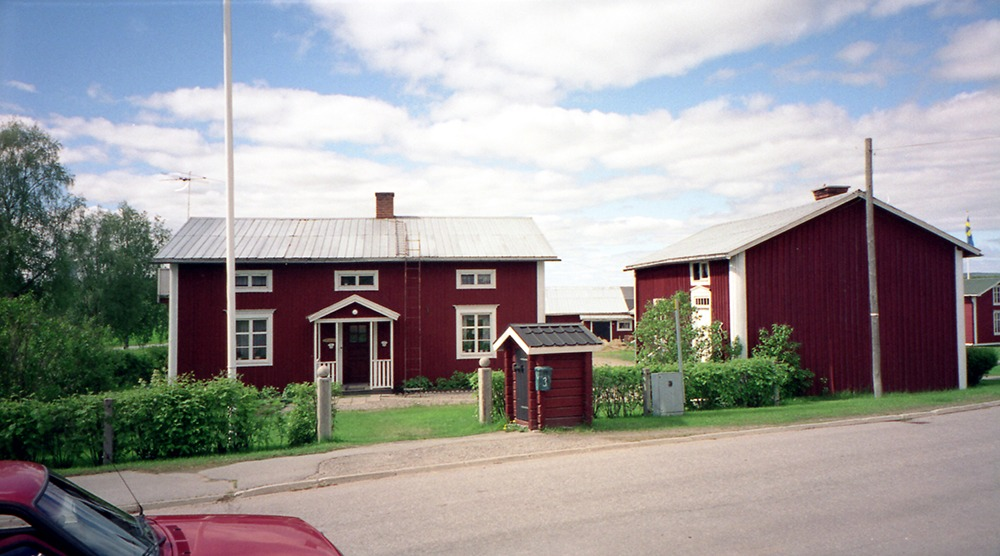 Röd Norrbottensgård vid bilväg.